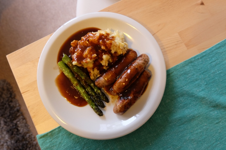 Lamb sausages with asparagus, garlic mash, and pepper gravy